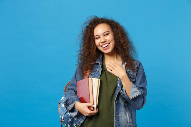 Junge studentin in jeanskleidung und rucksack hält bücher isoliert auf blauer wand