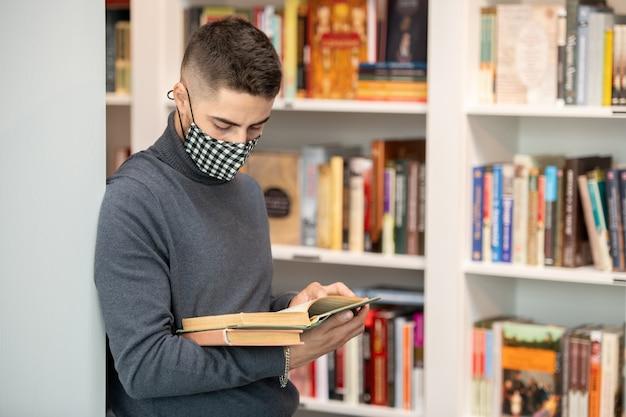 Junge studentin in schutzmaske liest buch, während sie an bücherregalen steht