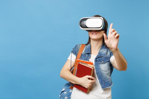 Junge studentin in virtual-reality-brille hält bücher, die so etwas wie druckknopf berühren und auf den schwebenden virtuellen bildschirm zeigen, der auf blauem hintergrund isoliert ist. ausbildung an der schulischen hochschule.