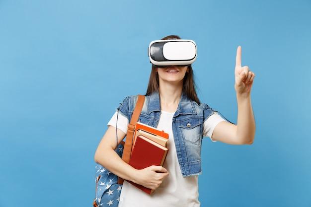 Junge studentin in virtual-reality-headset hält bücher, die so etwas wie druckknopf berühren und auf schwebenden virtuellen bildschirm zeigen, der auf blauem hintergrund isoliert ist. ausbildung an der schulischen hochschule.