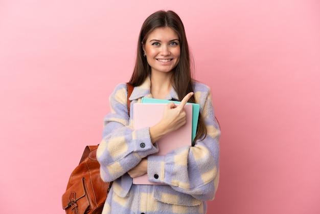 Junge studentin isoliert auf die seite zeigend, um ein produkt zu präsentieren