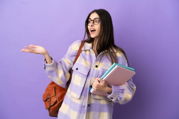 Junge studentin isoliert auf lila hintergrund mit überraschungsausdruck, während sie zur seite schaut