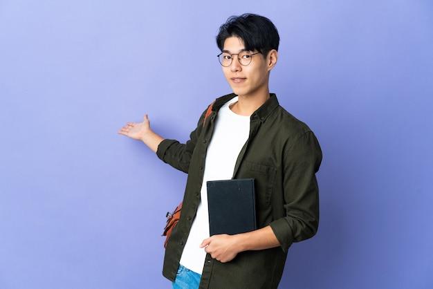 Junge studentin isoliert auf lila wand, die hände zur seite für einladung zum kommen ausdehnt