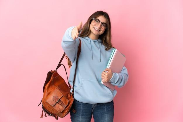 Junge studentin isoliert auf rosa händeschütteln für das schließen eines guten geschäfts