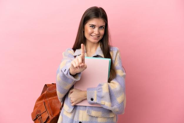 Junge studentin isoliert auf rosa hintergrund, die einen finger zeigt und hebt