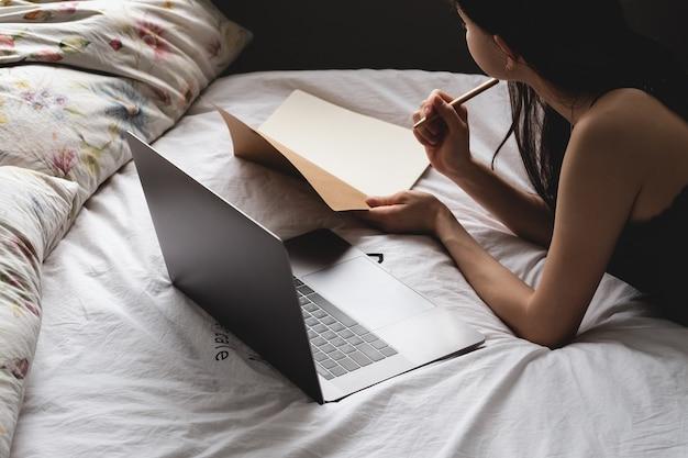 Junge studentin liegt mit laptop und notizbuch auf dem bett und macht sich notizen. fernstudium