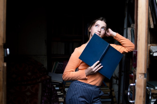 Junge studentin liest ein buch in der alten bibliothek, eine frau sucht nach informationen in den archiven