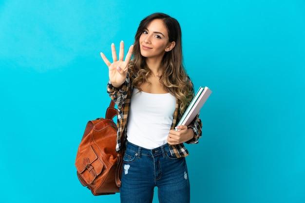 Junge studentin lokalisiert auf blauer wand glücklich und zählt vier mit den fingern