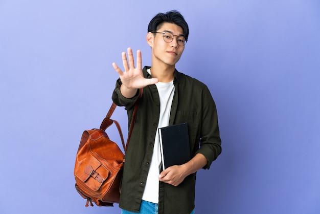 Junge studentin lokalisiert auf lila wand, die fünf mit den fingern zählt