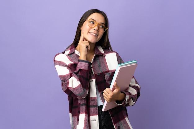 Junge studentin lokalisiert auf purpur, der eine idee beim aufblicken denkt