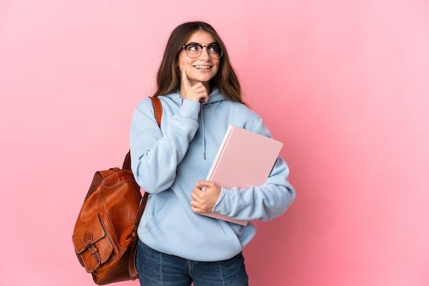 Junge studentin lokalisiert auf rosa, das eine idee beim nachschlagen denkt