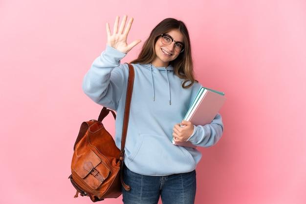 Junge studentin lokalisiert auf rosa, die fünf mit den fingern zählt