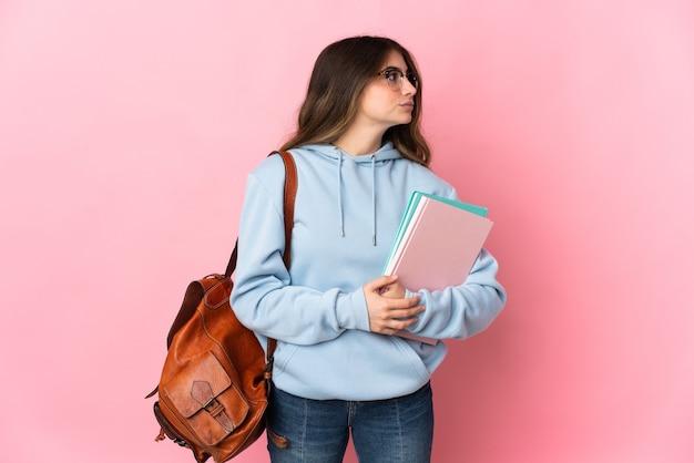 Junge studentin lokalisiert auf rosa, die zur seite schaut