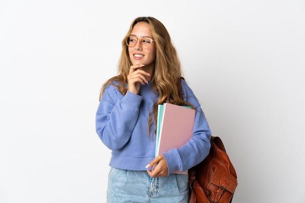 Junge studentin lokalisiert auf weißem hintergrund, der zur seite schaut und lächelt
