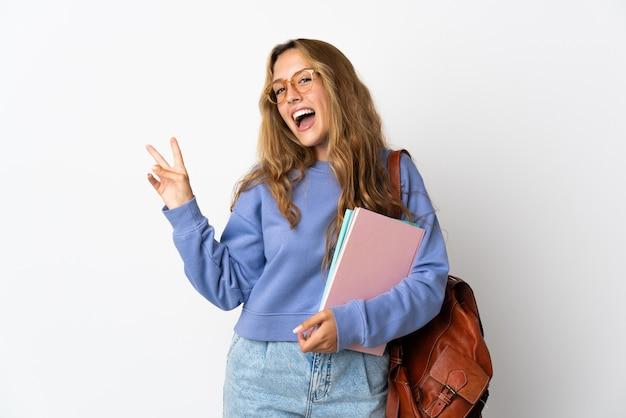 Junge studentin lokalisiert auf weißem hintergrund lächelnd und siegeszeichen zeigend