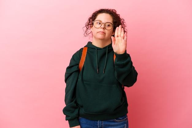 Junge studentin mit down-syndrom isoliert auf rosa wand stehend mit ausgestreckter hand, die stoppschild zeigt, das sie verhindert.