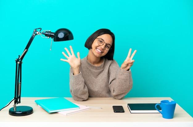 Junge studentin mit gemischten rassen, die an einem tisch studiert, der mit den fingern sieben zählt