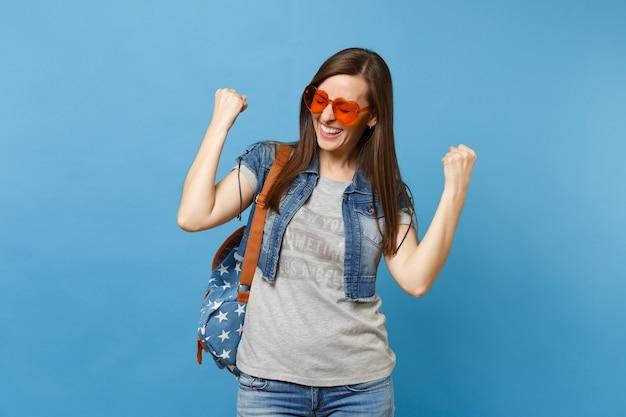 Junge studentin mit geschlossenen augen mit rucksack in orangefarbener herzbrille, die fäuste wie gewinner oder glücklicher mensch einzeln auf blauem hintergrund ballt. ausbildung an der hochschule. kopieren sie platz für werbung.