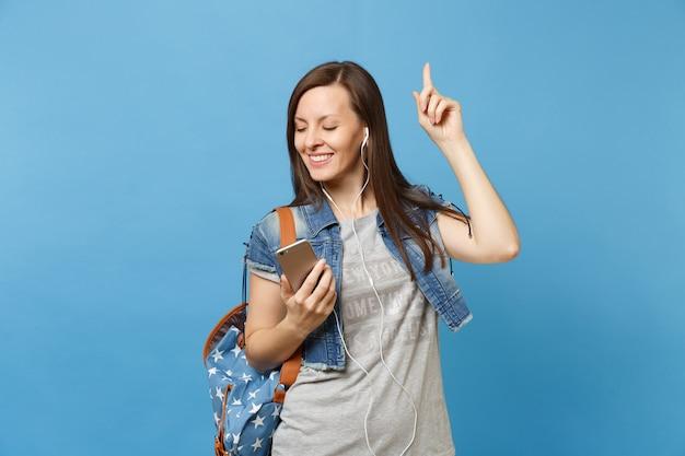 Junge studentin mit geschlossenen augen mit rucksack, kopfhörer hören musik, die mit dem zeigefinger nach oben tanzt und das handy isoliert auf blauem hintergrund hält. ausbildung an der universität. werbefläche.