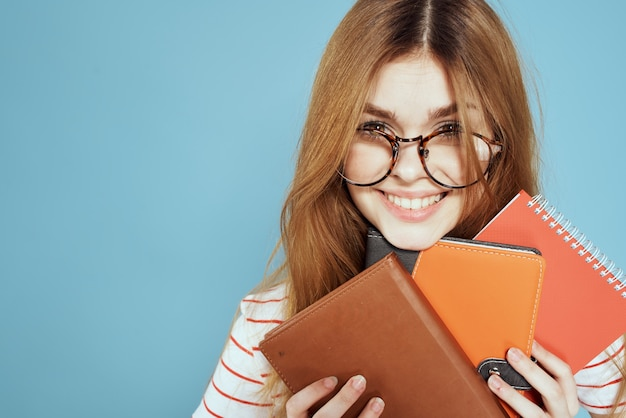 Junge studentin mit lehrbüchern, notizbüchern und zusammenfassungen in händen