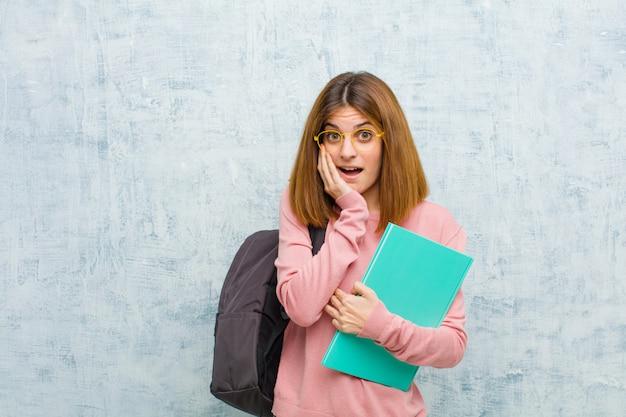 Junge studentin mit offenem mund vor schock und unglauben, mit verschränkter hand auf wange und arm, betäubt und erstaunt gegen die grunge-wand