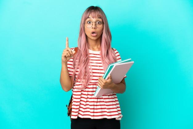 Junge studentin mit rosa haaren isoliert auf blauem hintergrund, die beabsichtigt, die lösung zu realisieren, während sie einen finger hochhebt