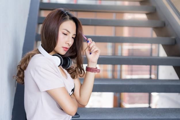 Junge studentin sitzen auf treppe mit kopfhörer im campusbereich