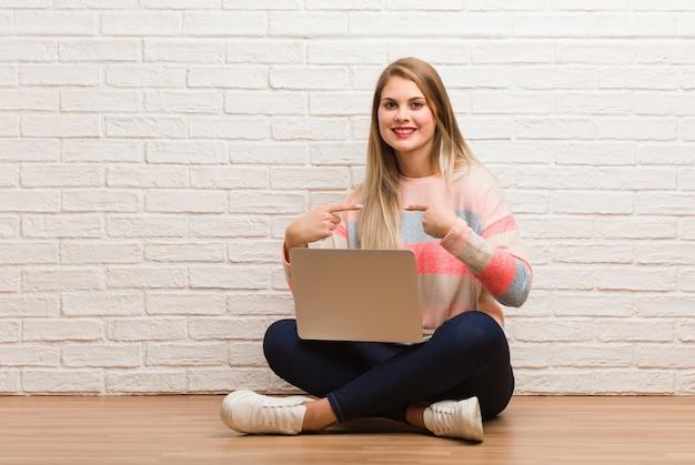 Junge studentin sitzt überrascht, fühlt sich erfolgreich und erfolgreich