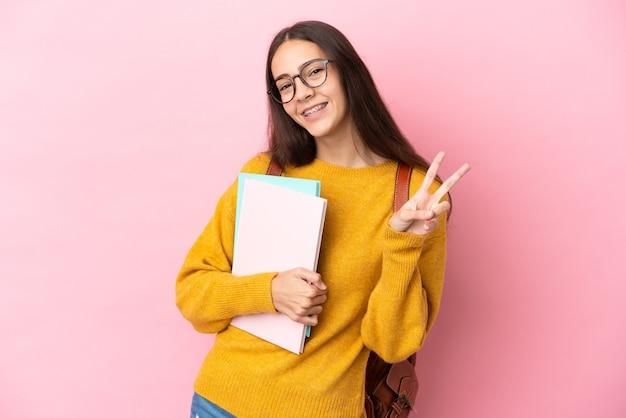 Junge studentin über isoliertem hintergrund lächelnd und siegeszeichen zeigend
