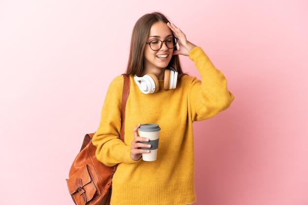 Junge studentin über isoliertem rosa hintergrund, der viel lächelt