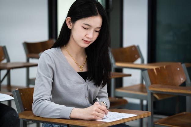 Junge studentinnen konzentrieren sich auf die prüfung im klassenzimmer. studentinnen schreiben ernsthaft die übung der prüfungen im klassenzimmer.