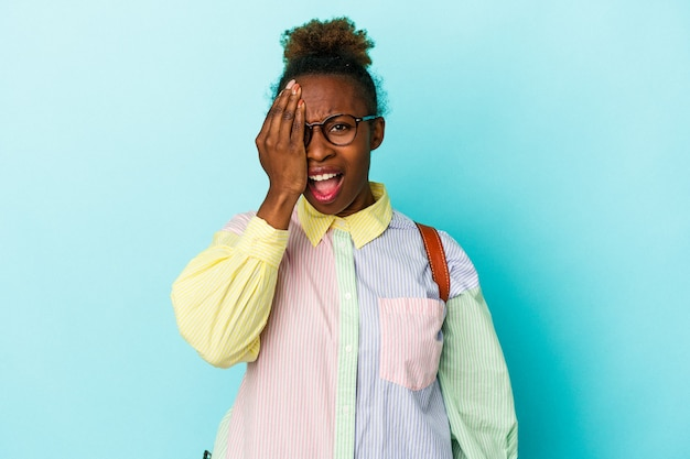 Junge studentische afroamerikanerin über isoliertem hintergrund, die spaß daran hat, die hälfte des gesichts mit der handfläche zu bedecken.