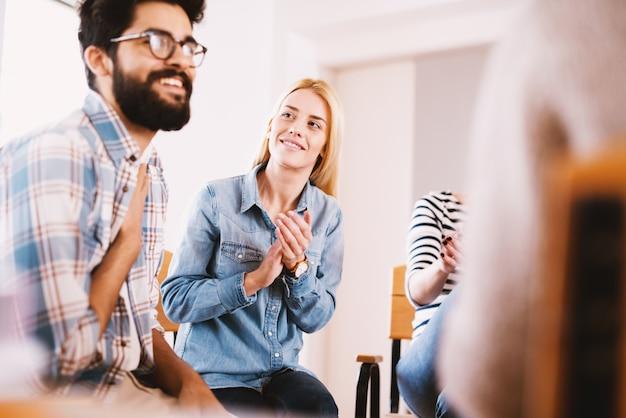 Junge süchtige menschen, die die situation feiern, während sie zusammen auf einer speziellen gruppentherapie sitzen. hübscher hipster-typ, der nach seinem geständnis und fortschritt lächelt.