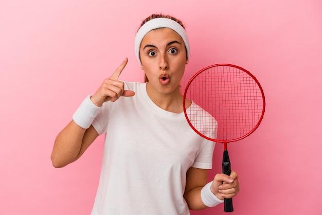 Junge süße blonde kaukasische frau mit einem badminton-schläger isoliert auf rosa hintergrund mit einer idee, inspirationskonzept.
