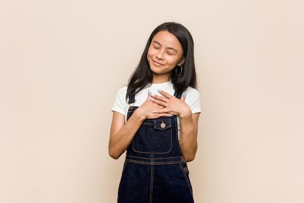 Junge süße chinesische teenager junge blonde frau trägt einen mantel gegen ein rosa lachend hände auf herz, konzept des glücks zu halten.