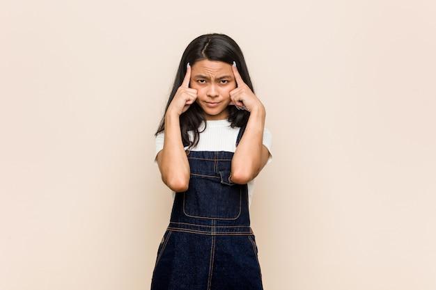 Junge süße chinesische teenager junge blonde frau trägt einen mantel gegen eine rosa wand konzentrierte sich auf eine aufgabe, zeigefinger kopf zeigen zu halten.