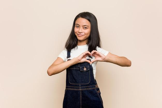 Junge süße chinesische teenager junge blonde frau trägt einen mantel gegen eine rosa wand lächelnd und zeigt eine herzform mit den händen.