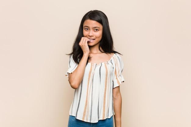 Junge süße chinesische teenager junge blonde frau trägt einen mantel vor einem rosa hintergrund beißen fingernägel, nervös und sehr ängstlich.