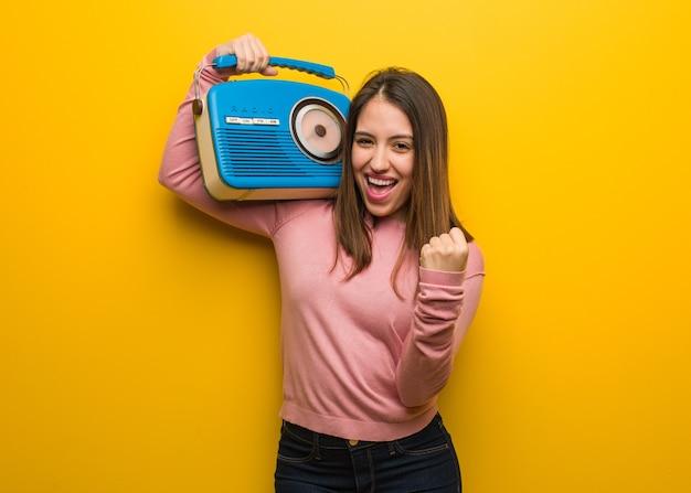Junge süße frau, die ein vintage-radio hält, überrascht und schockiert