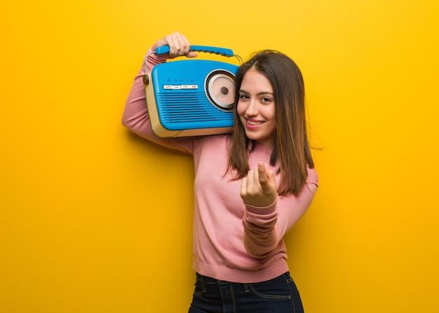 Junge süße frau, die ein vintages radio hält, das einlädt, zu kommen