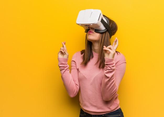 Junge süße frau, die eine virtuelle realität googelt, die finger kreuzt, um glück zu haben