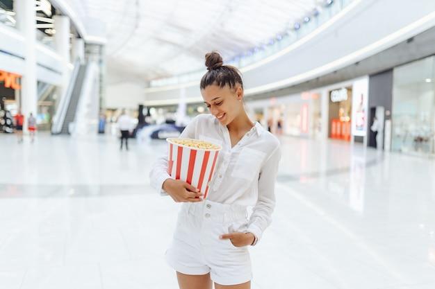 Junge süße frau, die popcorn im einkaufszentrumhintergrund hält