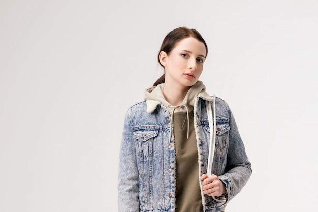 Junge süße frau in einer jeansjacke und mit einem rucksack, der auf einer weißen wand aufwirft