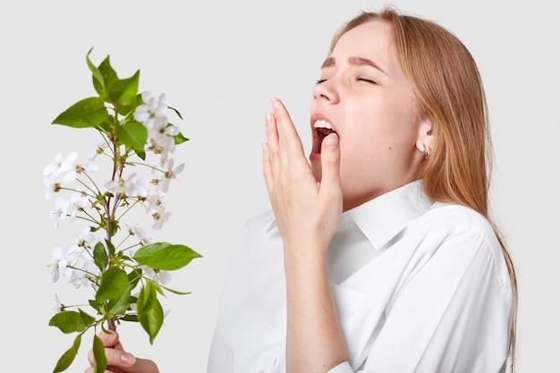 Junge süße frau ist allergisch gegen frühlingsblüte, niest, hält den mund weit offen, posiert auf weiß, mag keinen geruch. menschen-, krankheits- und allergiekonzept