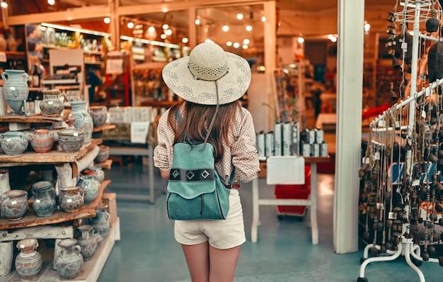 Junge süße mädchen tourist in einer bluse, einem strohhut und shorts mit einem rucksack geht um den ethnischen markt der stadt. reise-, tourismuskonzept.