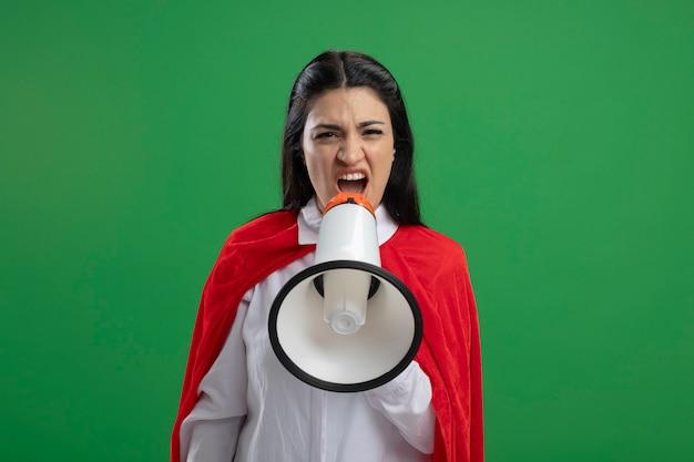 Junge superfrau, die im lautsprecher schreit, der front lokal auf grünem wandkopierraum betrachtet