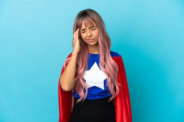 Junge superheldin mit rosa haaren isoliert auf blauem hintergrund mit kopfschmerzen