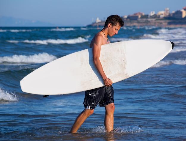 Junge surfer hält surfbrett aus den wellen heraus