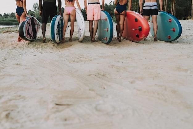 Junge surfer stehen in einer schlange. rückansicht konzept.