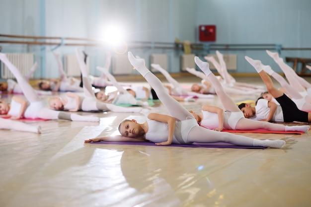 Junge tänzer im ballettstudio. junge tänzer machen während des aufwärmens im klassenzimmer gymnastikübungen. sport, gymnastik, kinderentwicklung